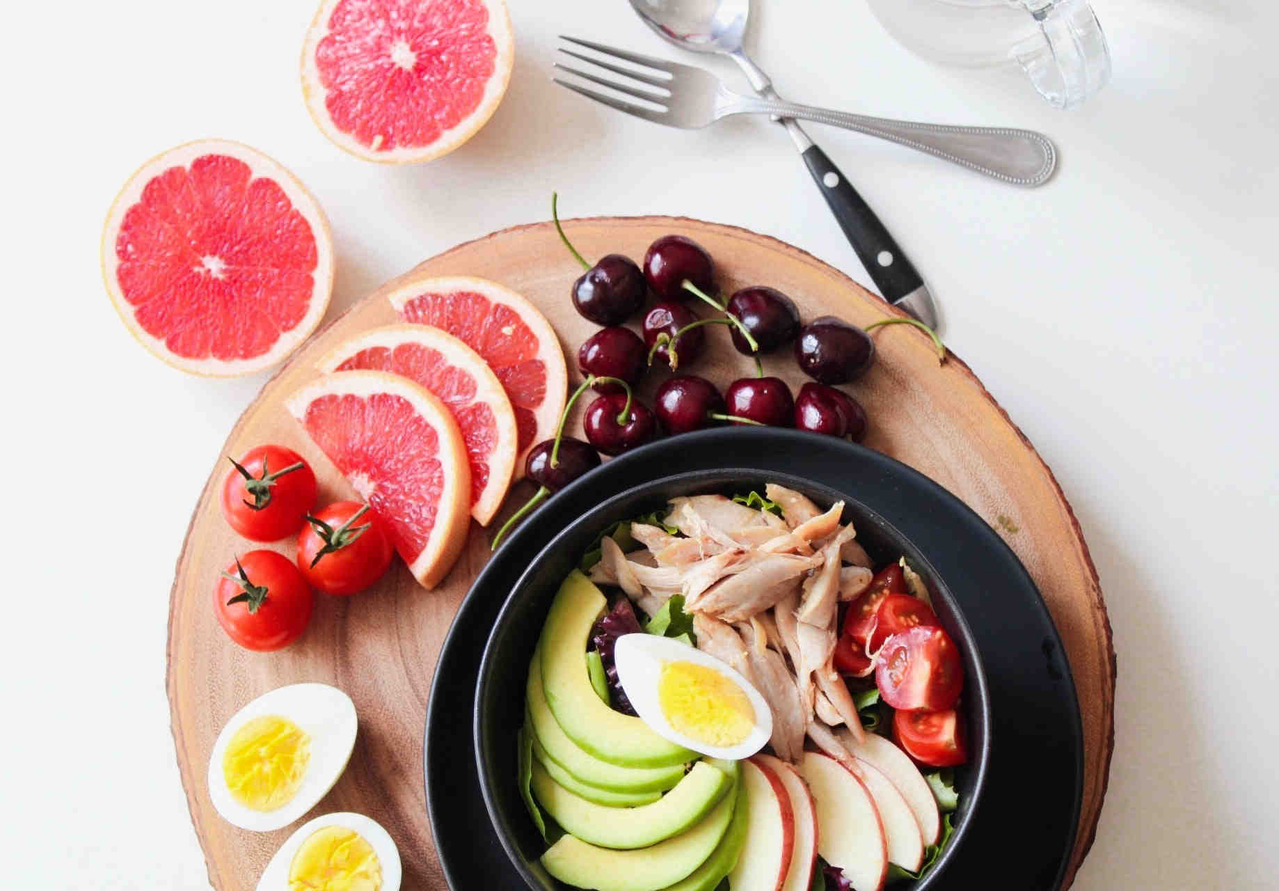 a healthy salad bowl with boiled eggs, apples, thin turkey slices, half-sliced tomato, cranberries and sliced grapefruit